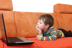 Child viewing a laptop on a couch