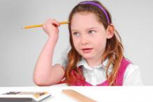 Girl doing math homework with calculator and ruler