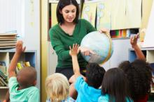 Students raising hands in classroom with teacher