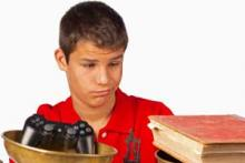 Child looking at videogame controller and at a book